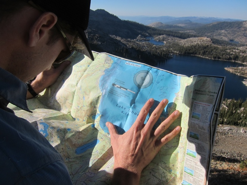 Kyle holding down the map in a slight breeze with Dicks Lake and Fontanillis Lake in the foreground.